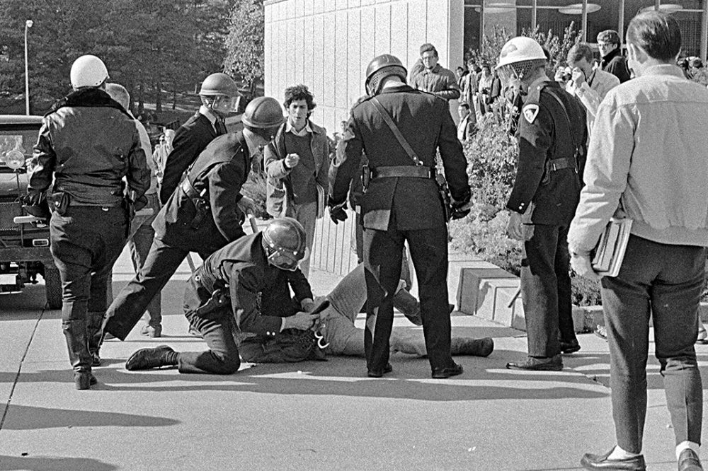 A student carrying books, perhaps on his way to or from classes, comes upon a scene of police officers attempting to handcuff a demonstrator.