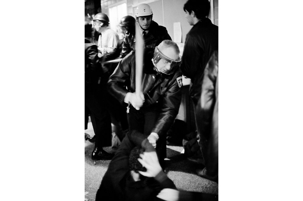 A police officer moves to strike a student on the floor, protecting his head, in the hallway of the Commerce Building.