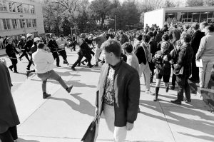 A bystander glances behind him as police officers violently clash with demonstrators during a protest against the Dow Chemical Company on the UW–Madison campus on Oct. 18, 1967