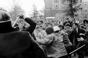 A Madison police officer raises his nightstick during the violent melee, a crowd of angry students in the background on Bascom Hill.