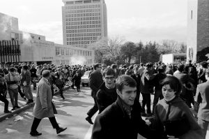 As police release tear gas near the Commerce Building on Oct. 18, 1967, students begin to flee and cover their faces.